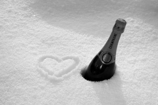Bottle of champagne and heart symbol drawn in deep snow beside it. Message 'love champagne'.