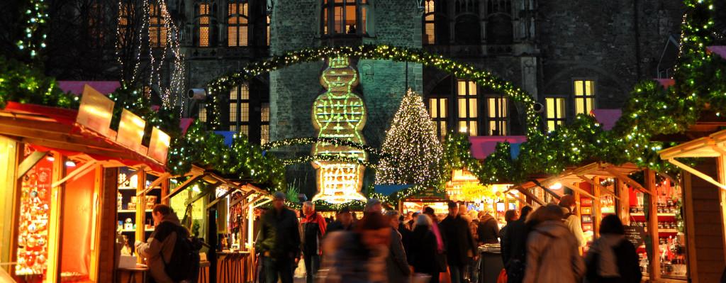 Der Aachener Weihnachtsmarkt mit seinen hell erleuchteten Buden auf dem Katschof. Im Hintergrund ist die Rückseite des Aachener Rathauses zu sehen.